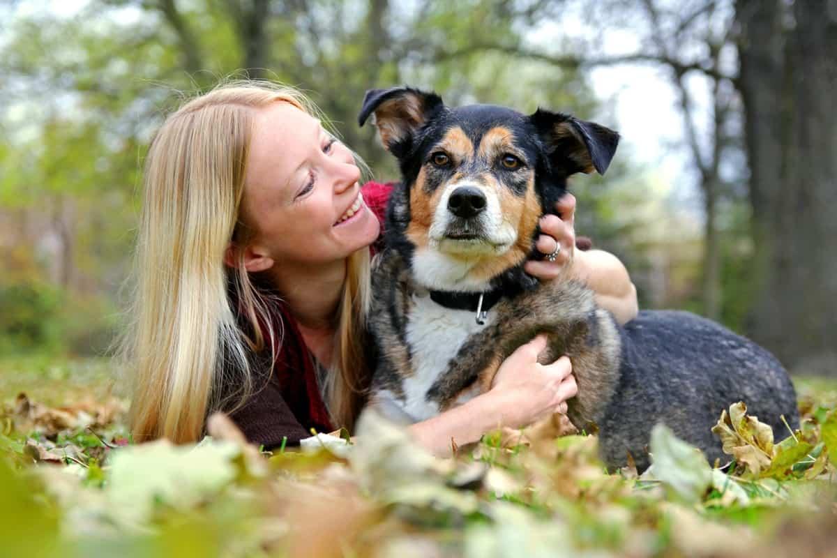 Woman smiling while holding sable German Shepherd